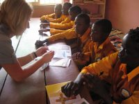 Jana assisting sponsored children to reply letters from their sponsors